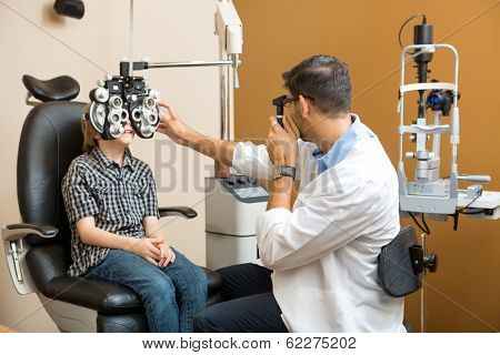 Mid adult male optometrist examining preadolescent boy's eyes in clinic