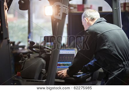 Mechanic using a laptop to interface with a forklift's electronics and engine