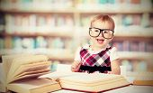 funny baby girl in glasses reading a book in a library poster