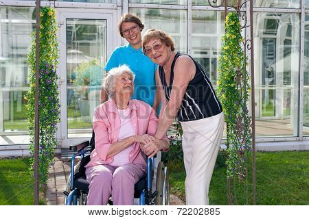Smiling Care Takers For Old Patient On Wheel Chair