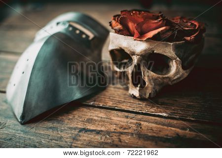 Skull with roses and armor on a wood table