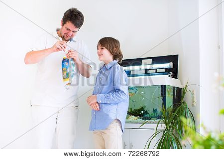 Father and son holding a plastic bag with a new fish they got in a zoo store ready to put it into a home aquarium poster