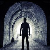 Young man stands in dark tunnel and looks in the glowing end poster