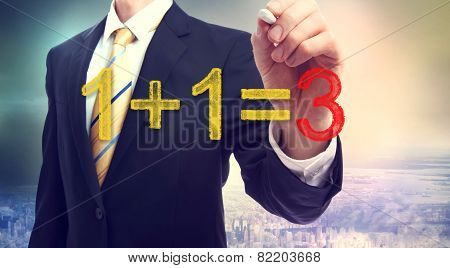 Businessman pointing at synergy concept 1+1=3 above the city poster
