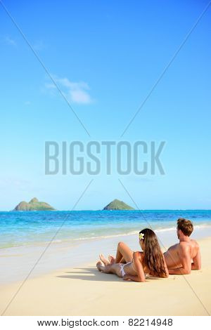 Beach vacations suntan couple relaxing in Lanikai, Oahu, Hawaii, USA. Vertical crop with blue sky copy space background for holiday vacation travel concept.