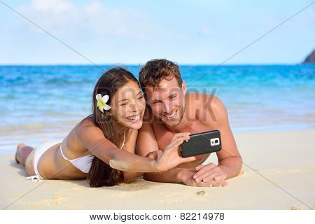 Beach holiday couple taking selfie with smartphone lying down relaxing and having fun holding smart phone camera. Young beautiful multicultural Asian Caucasian couple having fun on summer beach. poster