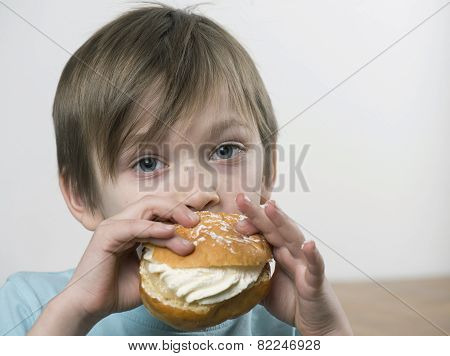 Young Boy Eating A Cream Bun
