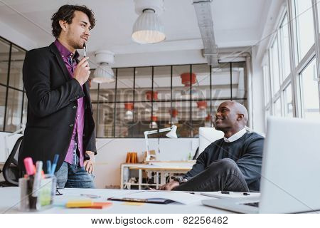 Two Young Office Workers Discussing Work In Office