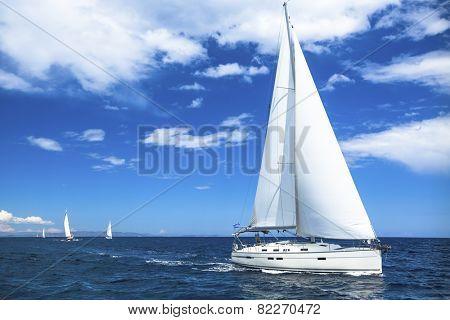 Sailing boat yacht or sail regatta race on blue water Sea.
