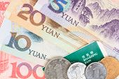 Chinese or Yuan banknotes money and coins from China's currency with boarding pass visa for travel concept close up view as background poster