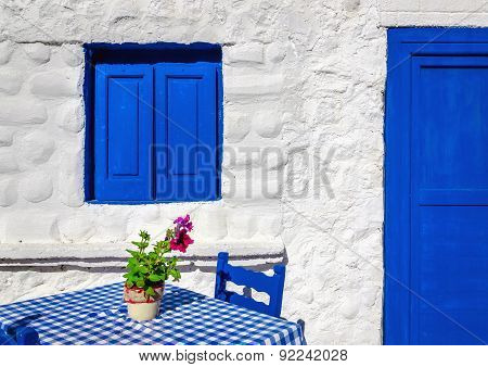 Iconic blue table with wooden chairs , Greece