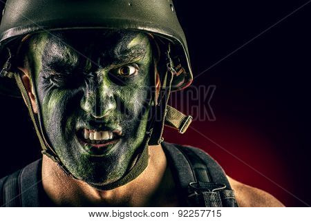 Close-up portrait of a furious soldier in war paint. Black background. Military, war. Special forces.