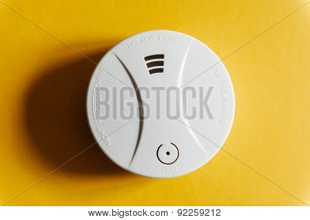 White smoke detector on yellow ceiling. A smoke detector is a device that senses smoke typically as an indicator of fire. Commercial and residential security devices issue a signal to a fire alarm control panel as part of a fire alarm system poster