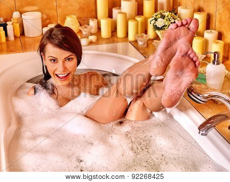Woman relaxing at water in bubble bath. Visible bare feet.