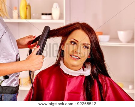 Woman at hairdresser with iron hair curler. Hair style.