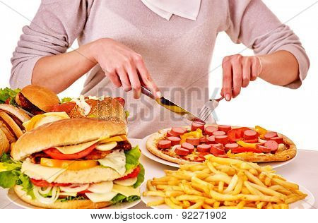 Body part of woman eating pizza at table. Isolated.
