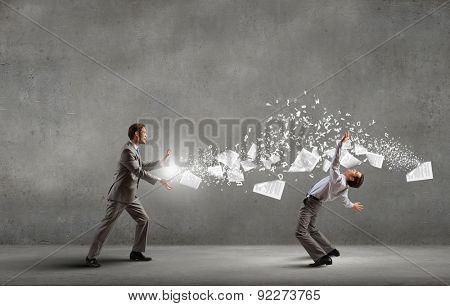 Young businessman trying to evade from thrown paper documents
