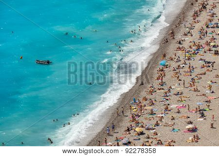 NICE, FRANCE - AUGUST 23, 2014: View from above on people on beach in Nice - fifth most populous, second-largest and one of most visited french cities 4 million tourists every year.