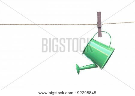 a green watering can hung on the rope with grey wooden clips