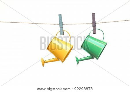 yellow and green watering cans hung on the rope with grey and purple wooden clips