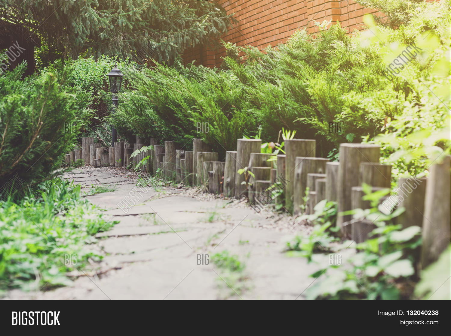 Beautiful Landscape Design Garden Path Tiles Closeup With Wooden Log Fence From Roundwood Evergreen