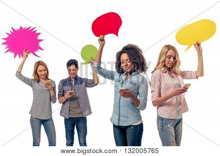 Young people of different nationalities with speech bubbles are using smartphones and smiling isolated on white background