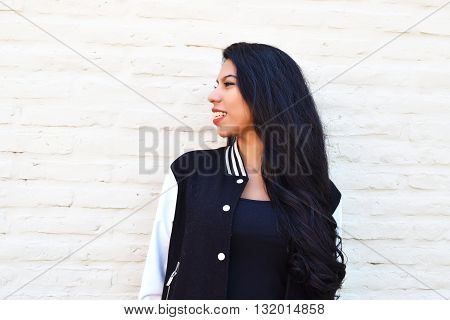 Portrait of young latin woman outdoors. Trendy and urban clothes.