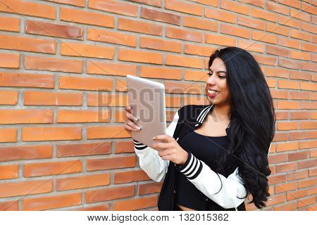 Young Latin Woman Using A Tablet Outdoors.