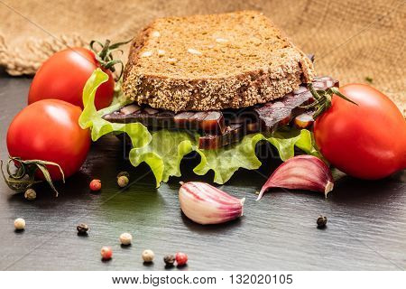 sandwich with vegetables and greens on a dark background