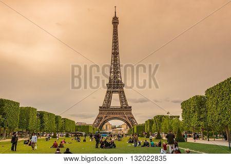 PARIS FRANCE - MAY 07 2015: Tourist sitting in the park near famous Tour Eiffel in Paris France