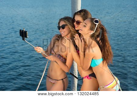 Smiling girls take a selfie. Ladies taking selfies on yacht. We're having so much fun. Vacation time spent at sea.
