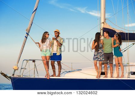 Smiling people on yacht deck. Young men hugging women. In the center of attention. Having fun with good friends.