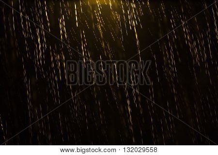 Night shot of a golden colored rain illuminated from the top by a lamp post with motion blur and droplets in focus and out of focus giving the sensation of depth. Can be used as a background pattern or texture and to convey emptiness solitude and loneline