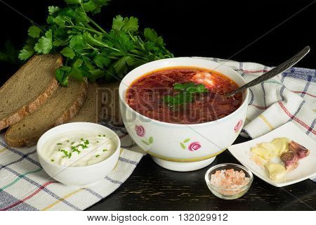 Traditional slavic soup popular in Russia, Ukrain, Poland, Estonia with cabbage, beatroot, tomatos served with rye bread, sour cream and garlic. Top view.