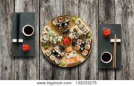 Japanese food restaurant, avocado sushi maki roll plate or platter set. Set for two with chopsticks, ginger, soy, wasabi. Sushi at black stone mat and rustic wood background. Top view, flat lay.