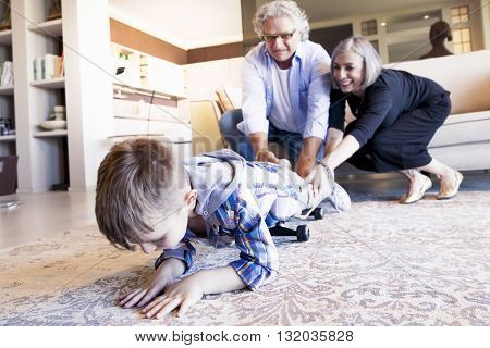 Couple Of Happy Grandparents Are Fun Nephew With Skateboard