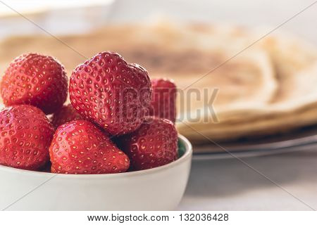 Fresh strawberries in white bowl with french pancakes crepes in the background on Saturday morning breakfast, selective focus, healthy nutrition. Abstract family happiness concept