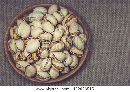 Pistachios roasted nuts health food nutrition overhead close up in wooden plate bowl on a cloth with selective focus and matte