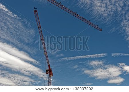 Tower crane painted red against the blue sky filled with clouds