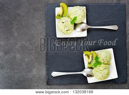Kiwi ice cream placed on a slate plate seeing from the top view with the note Enjoy your food