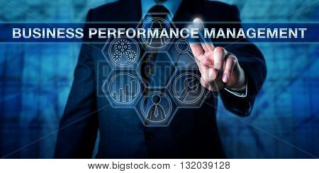Manager is pressing BUSINESS PERFORMANCE MANAGEMENT on an interactive touch screen interface. Technology concept and business performance management metaphor with tool icons for analytic processes.
