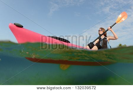 Pretty young woman paddling a kayak in tropical location in the ocean