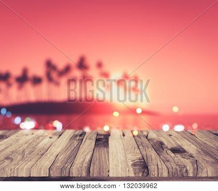 3D render of a wooden deck looking out to a defocussed palm tree island at sunset