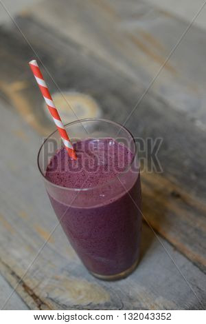 Vegan berry smoothie on a wood background with a straw