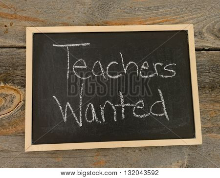 Teachers wanted written in chalk on a chalkboard on a rustic background