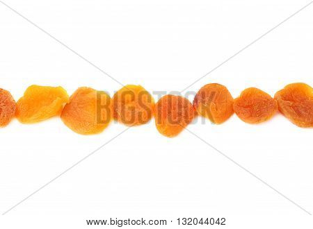 Line made of dried orange apricots over isolated white background