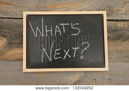 What's next written in chalk on a chalkboard on a rustic background