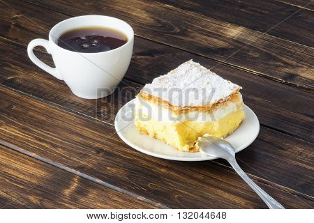 A cup of tea and a peace of vanilla cream cake on wooden table