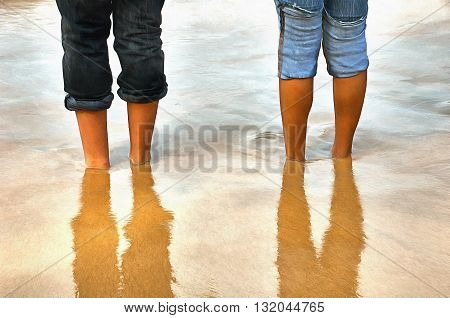 Bare feet buried in the sand upto the ankles on a beach