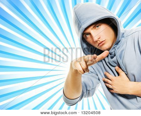 Handsome young man in a hood over abstract blue background